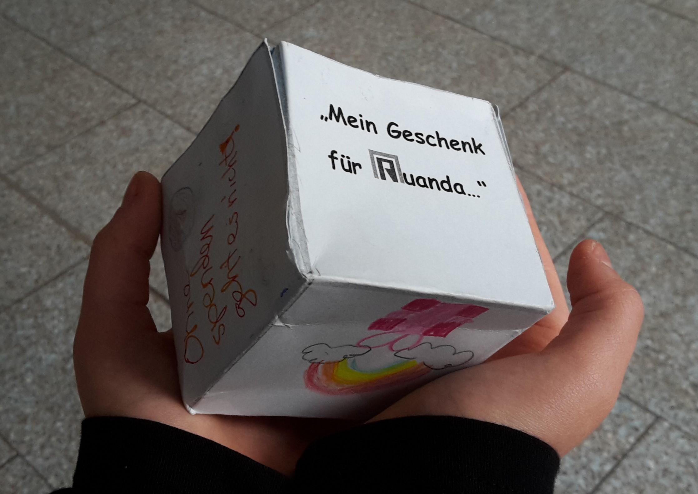 Das Bild zeigt zwei Hände, die eine kleine gebastelte Geschenk-Box halten.
