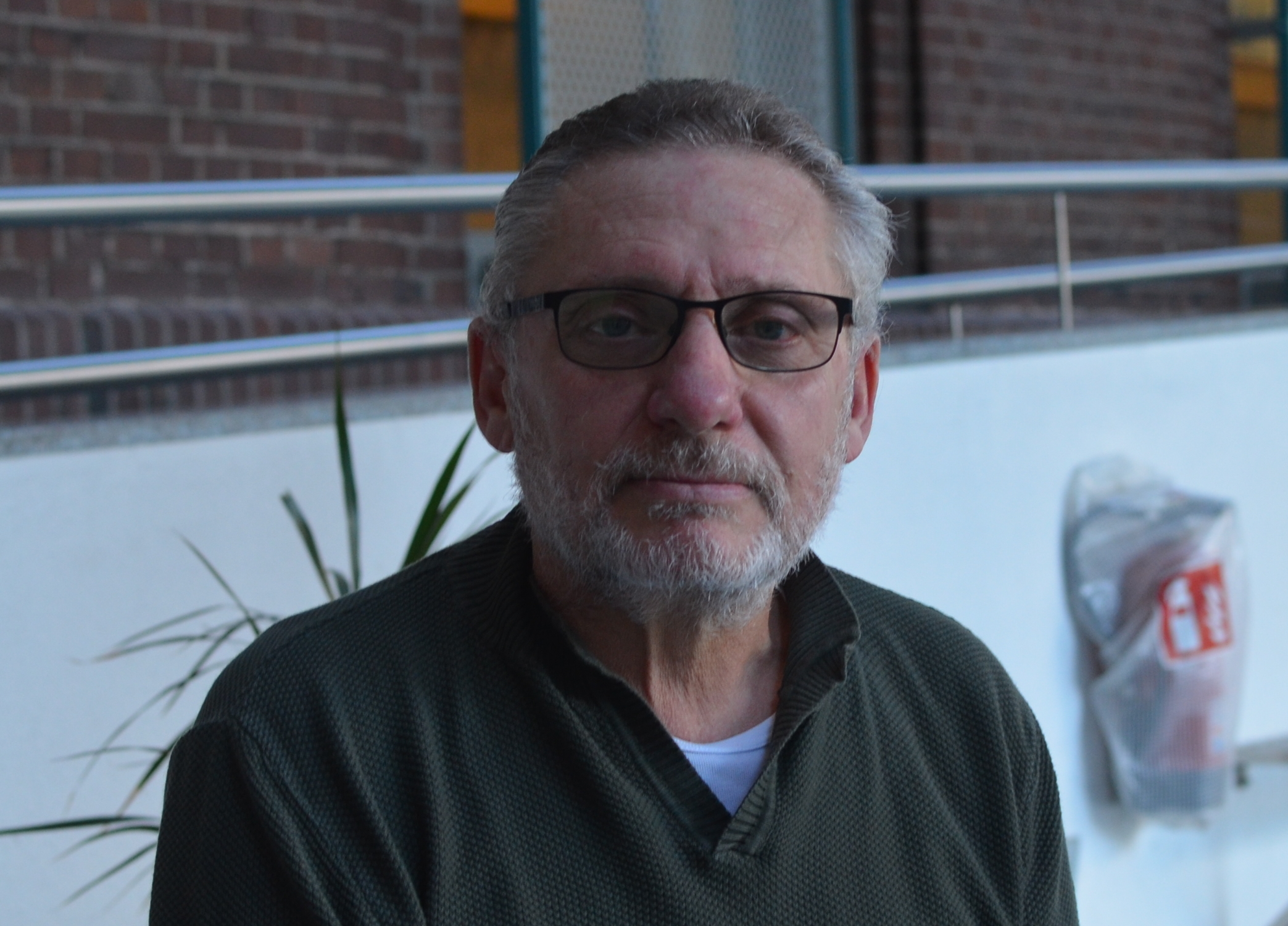 Das Bild zeigt Herrn Piccirilli in der Pausenhalle sitzend.